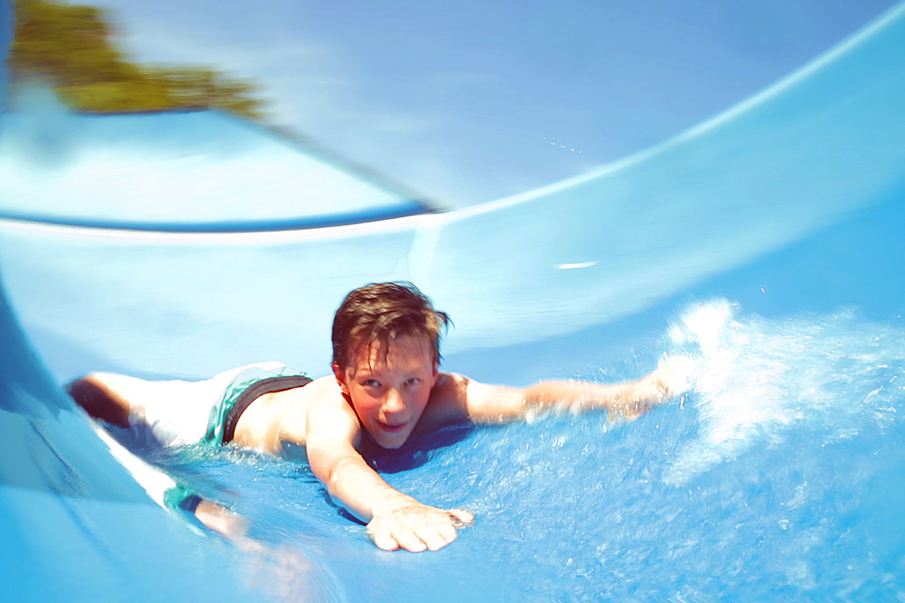 Junge rutscht im Badepark