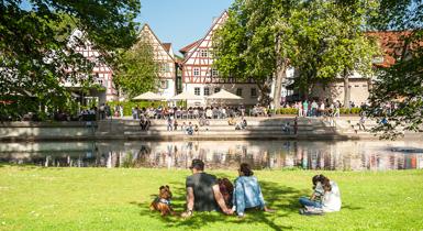 Familie sitzt im Stadtpark Kleb mit Blick auf den Longwyplatz