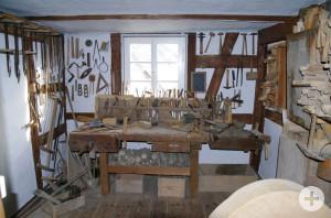 Fachraum mit weißer Wand und Werkzeugen an der Wand, Tisch in der Mitte, hinten in der Mitte ein Fenster