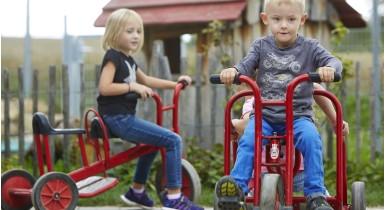 Kinder fahren im Kita-Außenbereich mit roten Dreirädern