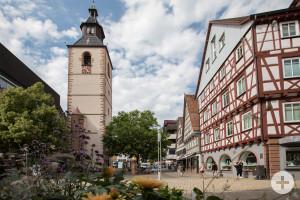 Alter Turm, links ein Gebäude und ein kleiner Baum, rechts davon ein Fachwerkhaus und bewölkter Himmel