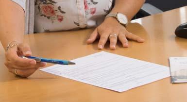 Eine Mitarbeiterin im Bürgeramt hilft beim Ausfüllen eines Formulars