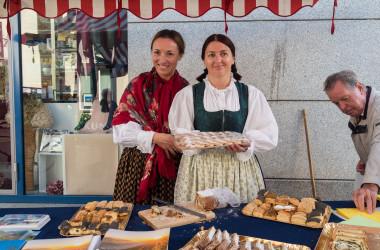 Bild von zwei Frauen in Tracht beim Verkauf von Essen in einem Marktstand