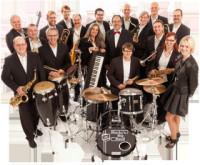 Gruppenfoto von Männer und Frauen, alle schwarz und schick angezogen, im Vordergrund stehen Trommeln und ein Schlagzeug, die Personen halten Instrumente wie Saxophon in der Hand