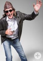 Bild von einem Mann mit Lederjacke, weißem Hemd, Jeanshose, Sonnenbrille und Mütze, er hält die linke Hand in die Luft und die rechte in Bauchhöhe