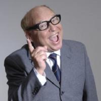 Porträt von Heinz Erhardt, er trät einen grauen ANzug, eine schwarze Brille, hebt seinen rechten Zeigefinger in die Luft und hat einen offenen lachenden Mund