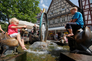 Zwei spielende Kinder, ein Junge und ein Mädchen, auf de Fabelbrunnen mit seinen Tieren