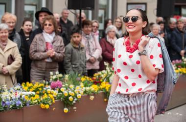 Frau mit Sonnenbrille läuft als Model vor Zuschauern