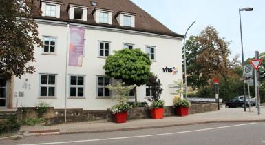 Blick von der Seite auf das weiße Geäude der Volkshochschule. Vor dem Gebäude steht ein Baum sowie drei bepflanzte rote Blumenkübel.
