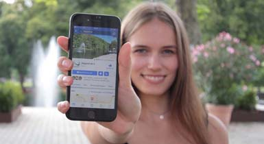 Junge Frau hält ihr Handy in die Kamera. Auf dem Bildschirm ist die Facebookseite der Stadt Nagold zu sehen
