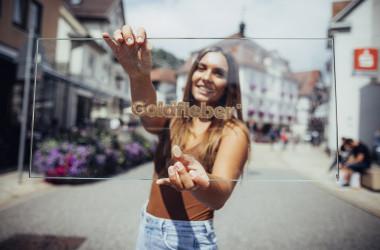 Mädchen hält Glasscheibe mit Golfieberlogo in den Händen