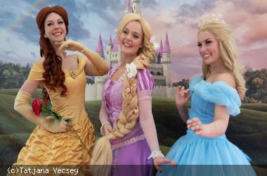 Die Prinzessinen Belle, Rapunzel und Cinderella stellen sich für Fotos auf