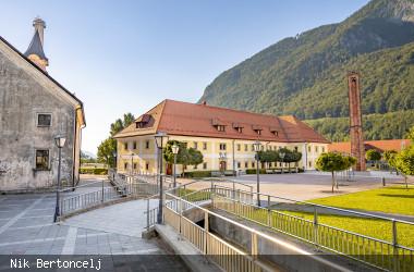 Blick auf einen Platz in Jesenice mit alter Kaserne und Bergen im Hintergrund