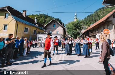 Umzug eines Musikvereins in Tracht durch die Straßen von Jesenice vorbei an Zuschauern