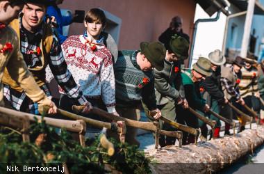 Junger Männer ziehen einen Baumstamm mit Äxten
