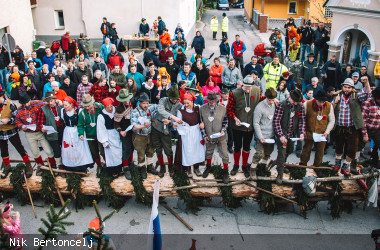 Viele Menschen stehen auf einem geschmückten Baumstamm und singen ein Lied vor Zuschauern