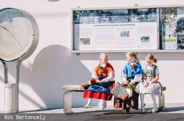 Drei Mädchen sitzen gekleidet in Tracht auf einer Bank