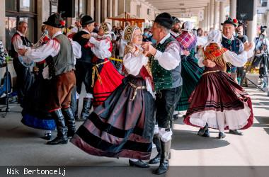Paare in Tracht tanzen einen Folkloretanz zu Musik