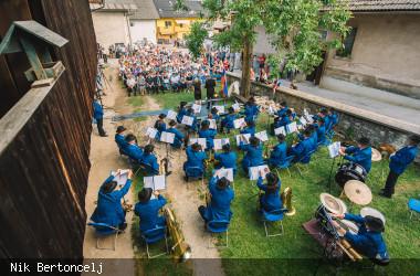 Open-Air Konzert einer Blaskapelle vor Publikum in einem Garten