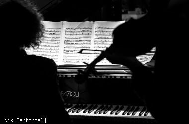 Blick auf die Noten von einem Pianisten und Violonisten von hinten