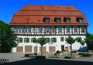 Gebäude Altes Oberamt mit Vorplatz, strahlend blauer Himmel, im Vordergrund 2 kleine Bäume und Bänke