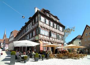 Hotel alte Post, vorne stehen Tische, Stühle, Buxkugeln in Töpfen, Sonnenschirme, strahlend blauer Himmel, über der alten Post ist eine Stromleitung mit einer Laterne