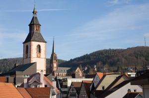 Alter Turm, darum herum sind überall Häuser, im Hintergrund blauer Himmel und eine Kuppe mit Wald