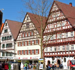Drei Fachwerkhäuser direkt nebeneinander, das linke davon ist die Alte Schule, im Vordergrund ein kleiner Baum ohne Blätter, strahlend blauer Himmel