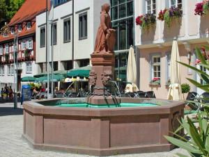 Urschelbrunnen nah, im Hintergrund das Rathaus, von rechts hängen rechts Blätter hinein