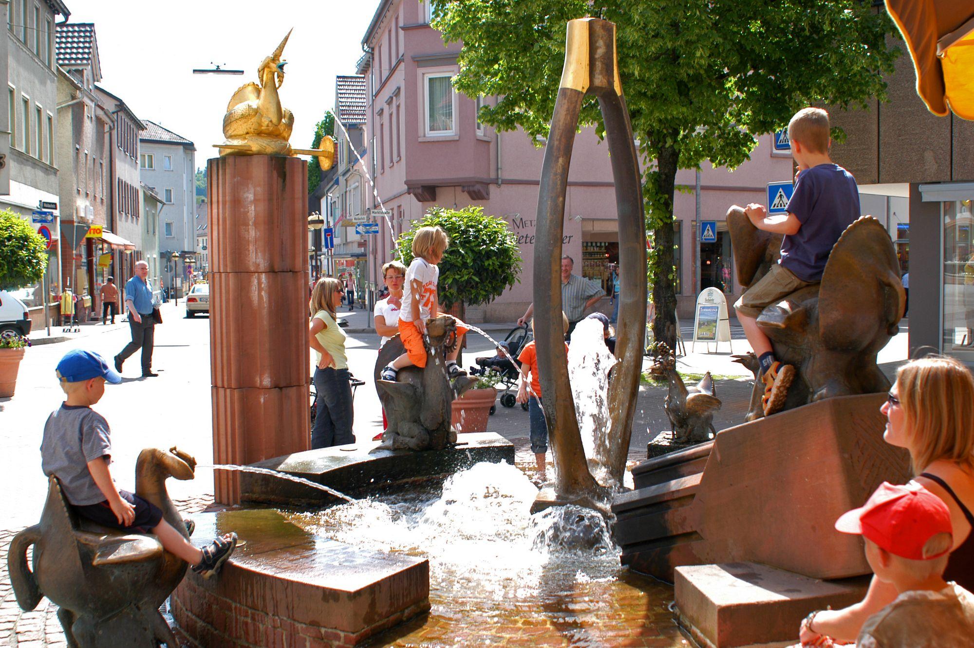 Auf dem Bild sieht man einen Teil des Fabelbrunnens mit spielenden Kindern, auf verschiedenen Säulen sitzen Tierskulpturen, aus deren Mündern Wasser spritzt