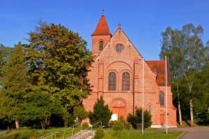 Katholische Kirche links und rechts stehen Bäume im Hintergrund strahlend blauer Himmel