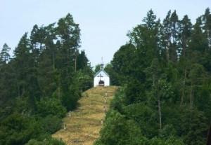 Ölberg Gündringen, links und rechts sind überall Bäume zum Hang hoch und man kann auf den Hang hinauf laufen auf Wiese und darauf ist ein kleines weißes Häuschen