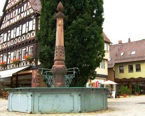 Unterer Marktbrunnen im Hintergrund ein großer Baum und ein Fachwerkhaus und rechts ein gelbes Haus zur Hälfte