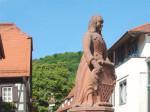 Der Urschelbrunnen, man sieht die Statue und rechts ein viertel Vorderteil von einem Haus und rechts das Rathaus und in der Mitte im Hintergrund Wald und strahlend blauer Himmel