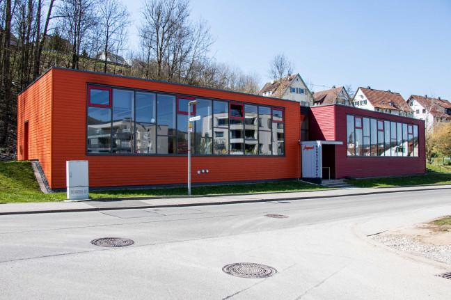 Blick von der gegenüberliegenden Straßenseite auf das Gebäude der Jugendkunstschule. Das Gebäude besteht aus zwei Teilen, die orange und rot gestrichen sind. Im Hintergrund sieht man Bäume und ein paar Häuserdächer.
