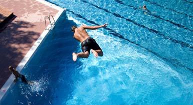 Mann springt vom Badepark-Sprungturm